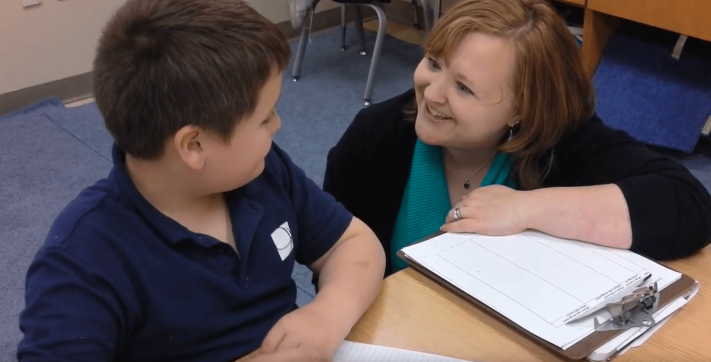 Julie confers with student during writing workshop